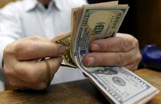 Homem conta notas de dólar em casa de câmbio no Cairo, Egito.